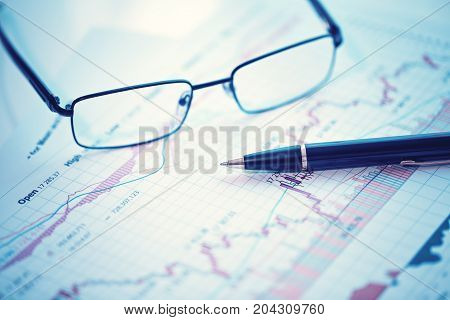 Pen and glasses on financial chart business concept analysis of sales plan business report business work station with paperwork
