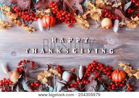 Happy Thanksgiving day holiday fall background with Happy Thanksgiving letters seasonal fall nature berries pumpkins apples and flowers on the wooden background. Fall background