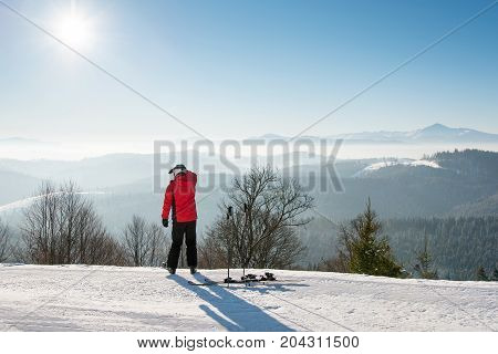 Male Skier Resting After The Ride Standing With His Back To The Camera On Top Of The Ski Slope Looki