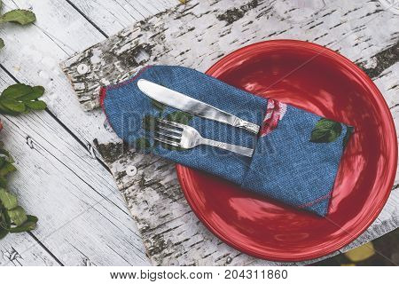 Vintage silverware on red plate on rustic wooden background, top view