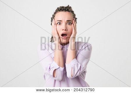 young horrified woman closing her mouth with hands over white background. Negative facial emotion. To be afraid to lose job