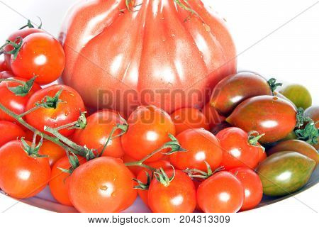 Variety of tomatoes Tomatoes in foreground, different varieties, closeup on white background