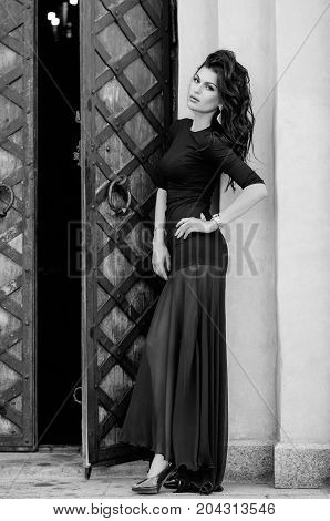 Attractive Brunette In Black Dress Stands In Full Growth On Building Background. Fashion Photo. Blac
