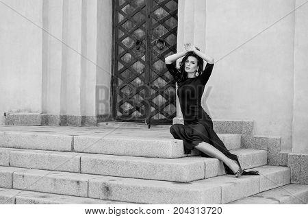 An Attractive Sexy Slender Brunette In A Long Black Dress With A Slit Sitting On The Steps Of A Vint
