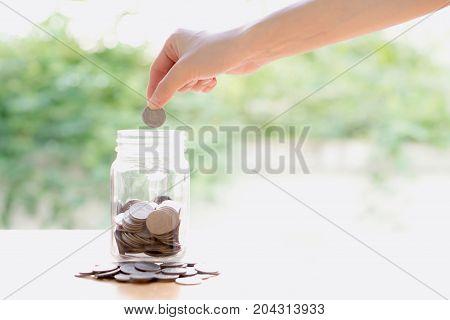 Woman Dropping Coins Into Glass Jar, saving