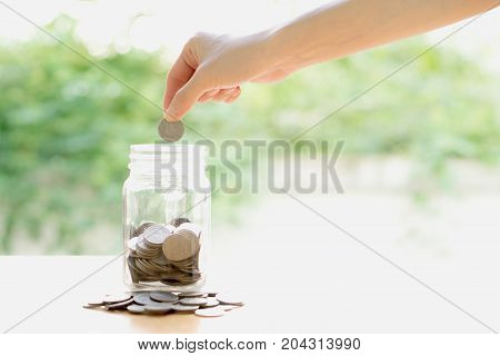 Woman Dropping Coins Into Glass Jar, saving money