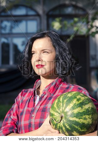 LATVIA, RIGA, SEPTEMBER, 19, 2015 - Portrait of cute young brunette in a checkered red shirt standing with a whole watermelon in hands. Riga, Latvia