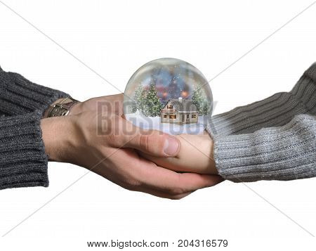 Men's hands and child's hands holding a glass sphere. Ball Christmas scenery inside. Fairytale house snow winter. White background