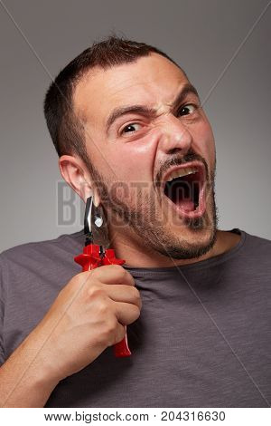fool man showing pliers and make a bizarre face