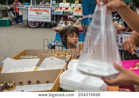 Bangkok Thailand - August 6 2017 : Unidentified seller and customer are trading a sugar coated donut and sweet dessert food in donut and sweet dessert shop at Thai street food market.