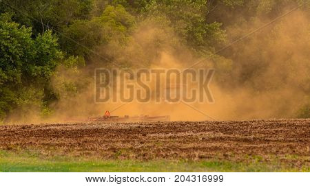 A barely visible tractor kicks up a lot of dust while plowing a field.