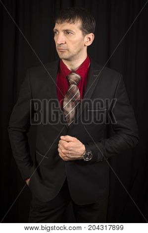 The fashion model is in elegant black suit with necktie on black background.