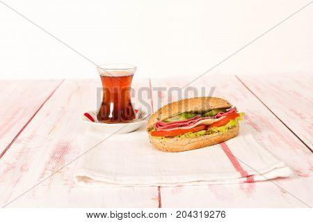 Fresh and tasty sandwich with tea on cloth napkin