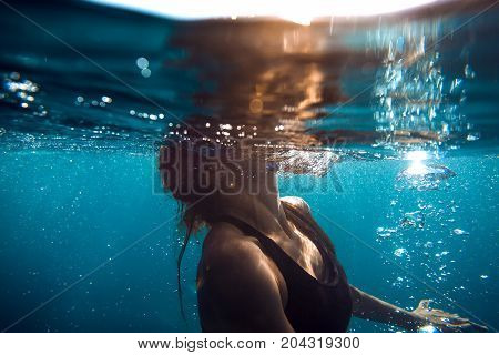 Underwater photo with woman in ocean and bubbles