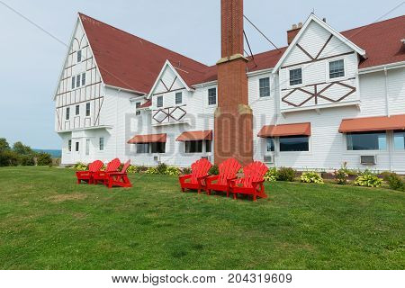 Red beach chairs and white lodge Cape Breton Highlands Ingonish Cape Breton Island Nova Scotia Canada
