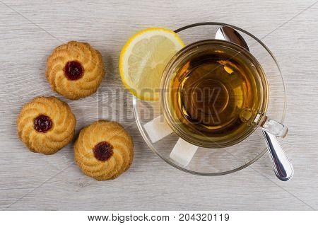 Cup Of Tea, Lemon, Sugar, Teaspoon And Cookies With Jam