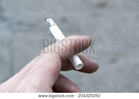 Ashes and smoke from a cigarette. Close-up.