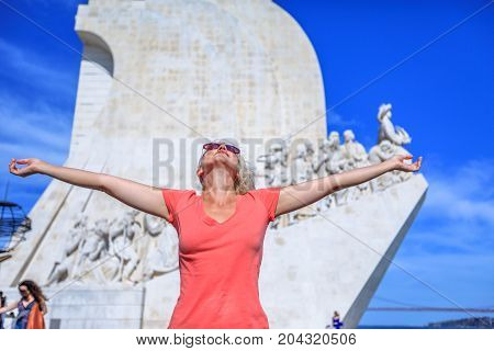 Happy tourist woman with open arms at Padrao dos Descobrimentos. Blonde female caucasian enjoying Discoveries Monument popular landmark in Belem District, Lisbon, Portugal. Europe traveler concept.