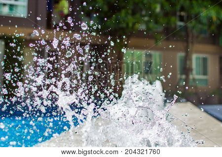 Freeze splashing droplets of water in the air near the swimming pool close up image