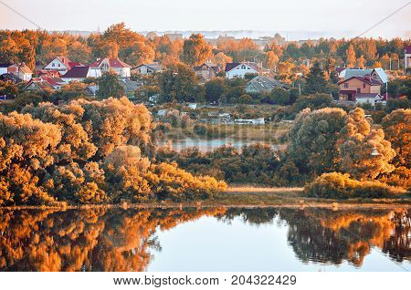 Autumn landscape. Birds eye view of small autumn village in the autumn forest at sunrise. Wooden houses between the yellowed autumn trees near the bank of the autumn river.