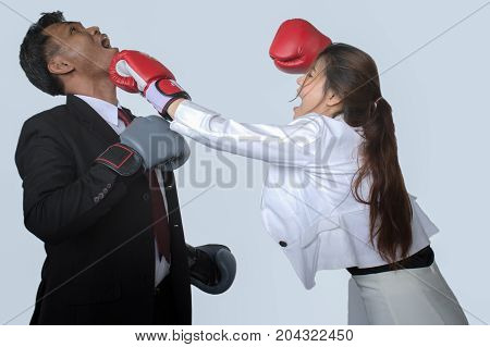Portrait of professional businessman in suits and boxing gloves kicking his rival,isolated on gray background