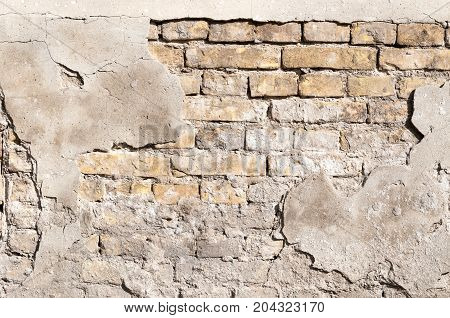 Damaged plaster on the old brick wall
