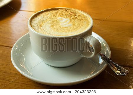 White cup of coffee with spoon on wooden table background. Cappuccino latte in cafeteria