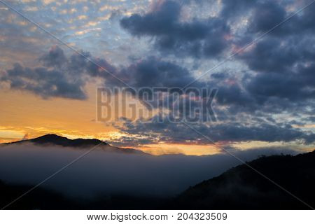 mountain range tropical rainforest canopy at southern of Thailand with more cloud sunset time copy space for text layout.
