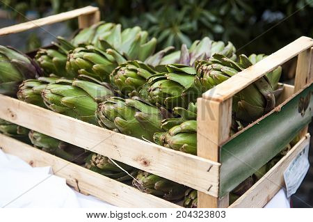 Artichokes in a wooden box on the market