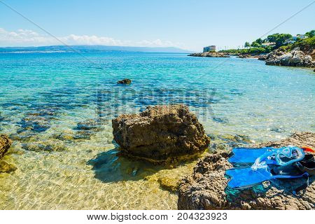 Flippers mask and snorkel ona rocks by the sea in Sardinia Italy