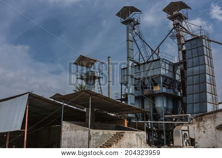 Mysore India - October 27 2013: In Ranganathapur an industrial rice mill shows silos for husks and shafts ladders and pipes to load them under bluish sky with white clouds.
