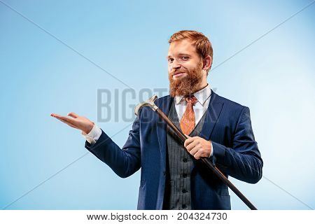 The bearded man in a suit holding cane and presenting something. Isolated on a blue background.