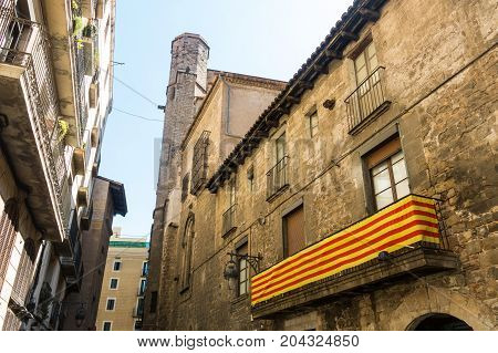 Catalan Flag, Hanging On A Balcony, In The Gothic Quarter Of Barcelona. Belfry Of The Pine Church In