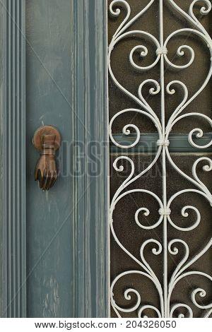 Vintage wooden door with knocker and spiral metal pattern background.