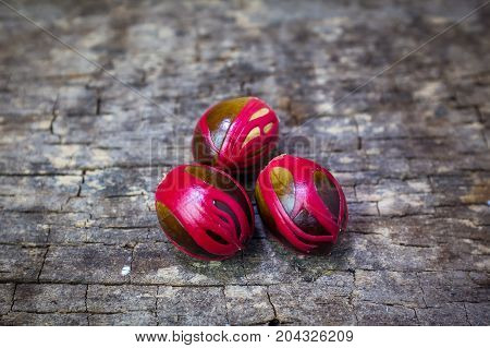 Three Whole Nutmeg Red Placenta-like Cover Of Seed On Wooden Background.