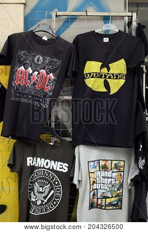 ATHENS GREECE - AUGUST 4 2016: Rock and hip hop music t-shirts for sale printed with band logos by The Ramones AC/DC Wu-Tang Clan and video game Grand Theft Auto.