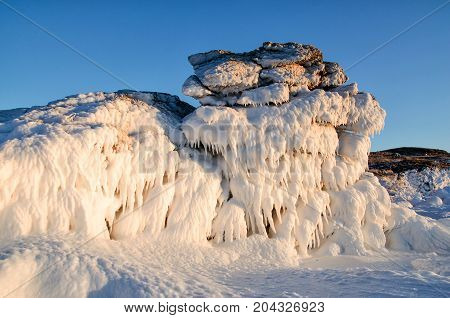 Ice dragon from frozen rock at sunset, fantastic winter landscape, closeup. Russia, lake Baikal