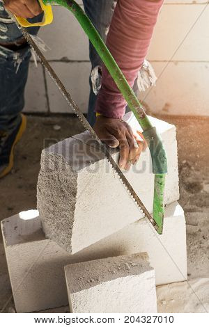 construction worker using saw for cutting foam bricks