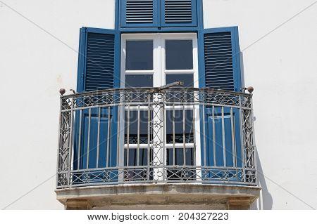 Glass door wooden shutters and veranda exterior. Architectural detail.