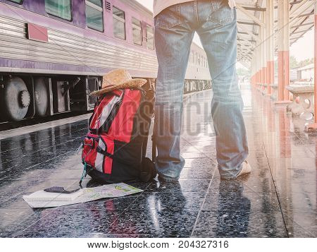 Lower part of traveler with backpack in train station. Travel concept.