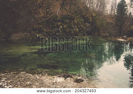 Beautiful landscape of emerald pool among brown hill reflect forest and sky with surrounding by mountain range and trees in autumn, Wonderful view of small green lake from The Radovna river with tree covered cliff in deep jungle in Bled at Slovenia, Scene