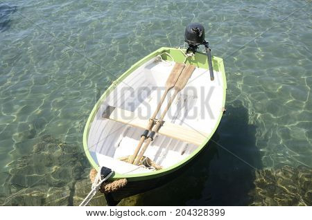 White and green rowboat on the water of the Mediterranean sea in Cadaques a town in the province of Girona Catalonia Spain.