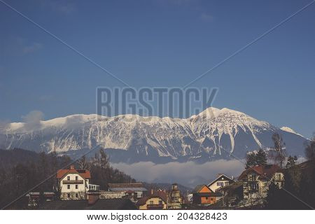 Mountain range covered in snow with fog mist behind green tree line village and blue sky background in Winter season
