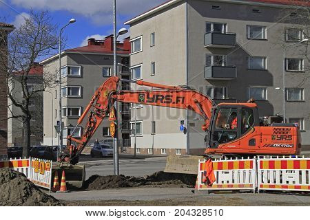 Tampere, Finland - April 7, 2017: man in excavator is digging the ground in Tampere, Finland