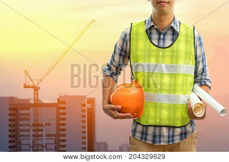 Engineer or Safety officer holding hard hat with the mobile crane machine is background in construction site, Civil construction engineering concept