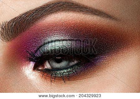 Close-up of beautiful womanish eye. Colored eyeshadows