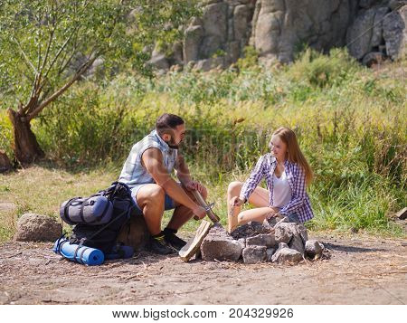 Couple in the forest. Hands of a man and girl who in the forest among the dry, withered leaves kindle fire.