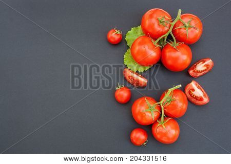 Cherry tomatoes and sliced tomatoes on a black background