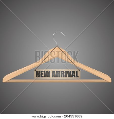 Clothes hanger with new arrival tag. Wooden hanger with tag and the message about the new delivery of the goods.