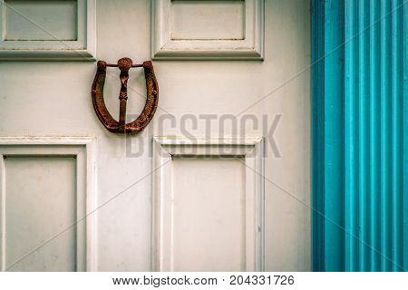 A rusty horseshoe door knocker mounted on a weathered Virginia door.